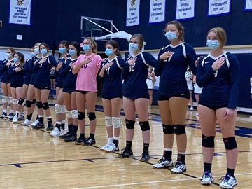 The Varsity Volleyball team lines up for the national anthem in masks prior to their game vs. district rival Second Baptist